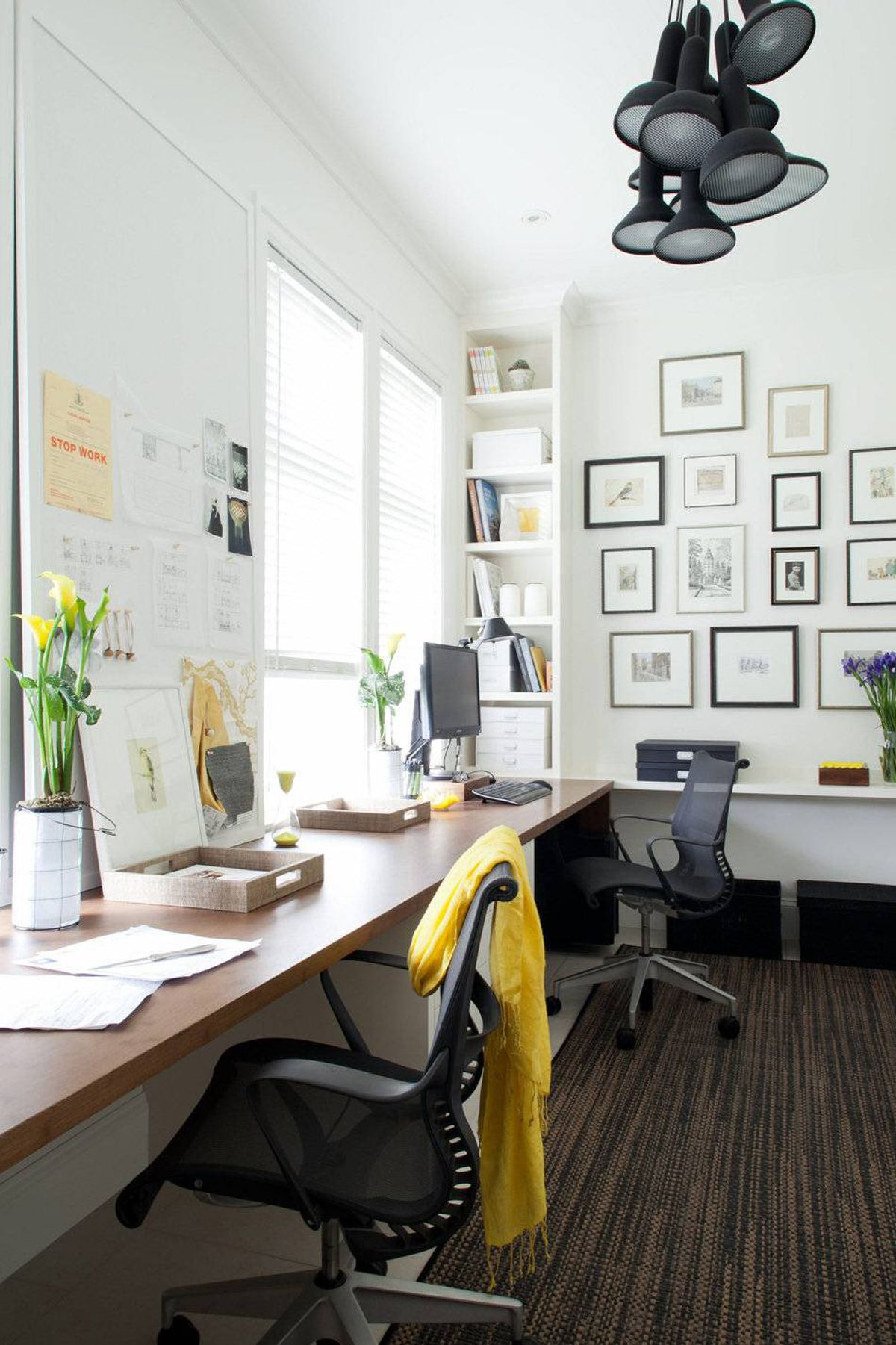Taking advantage of the room's length, it was decided to run the desks along the window wall, which opened up the view to the front garden, increased the surface area available for working and created space to build full-depth millwork on the opposite side of the room.