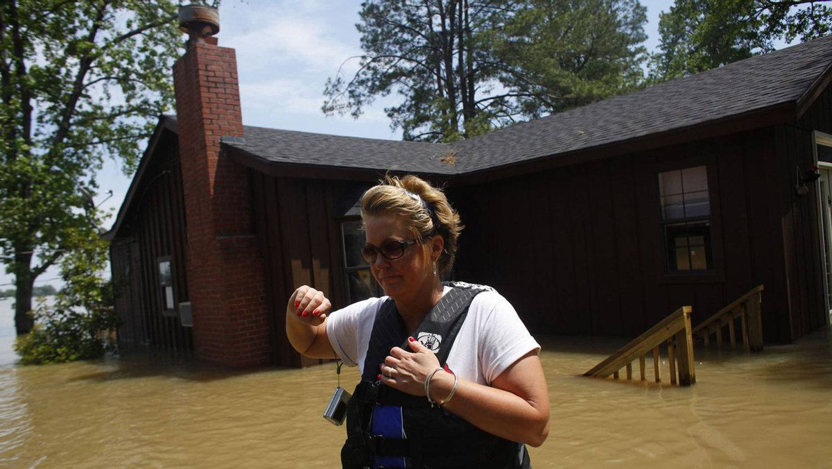 Sherry Rose walks through floodwaters in front of her home in Holly Grove, Arkansas May 10, 2011. The Mississippi River may have reached its highest level at Memphis early on Tuesday just inches below the all-time record.
