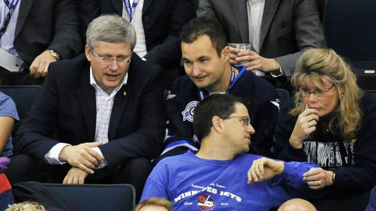 Canada's Prime Minister Stephen Harper (L) watches the game between the Winnipeg Jets and Montreal Canadiens during the first period of their NHL hockey game in Winnipeg, Manitoba, October 9, 2011. The Winnipeg Jets are playing their first season game since the franchise left the city 15 years ago.