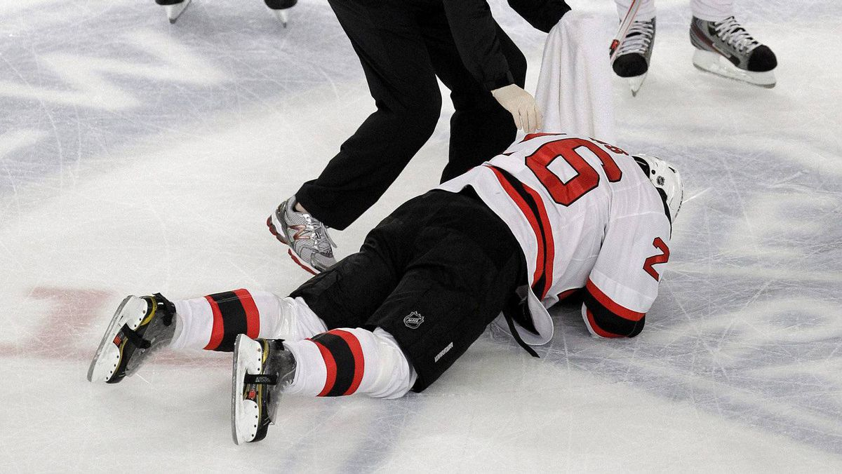 New Jersey Devils' Patrik Elias (26), of the Czech Republic, lays on the ice after an apparent hit to the face as trainer Richard Stinziano checks on him during the first period of Game 1 of their NHL hockey Stanley Cup Eastern Conference final playoff against the New York Rangers, Monday, May 14, 2012, at New York's Madison Square Garden.