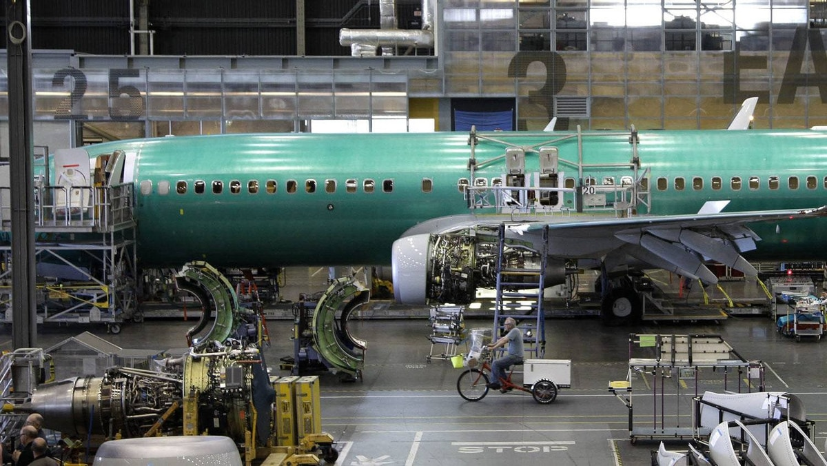 In this file photo taken June 3, 2011, an employee rides a tricycle past a Boeing 737 airplane at the company's assembly facility in Renton, Wash.