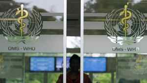 A person is seen approaching the main entrance of the World Health Organization headquarters in Geneva, Switzerland.
