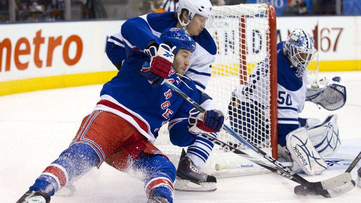 New York Rangers left winger Brandon Prust (left) is hauled down by Toronto Maple Leafs centre Mikhail Grabovski as he closes on goaltender Jonas Gustavsson during first period NHL hockey action in Toronto on Thursday October 21, 2010.