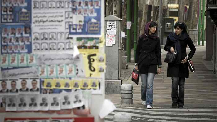 Iranian women walk past electoral posters in northern Tehran March 1, 2012.