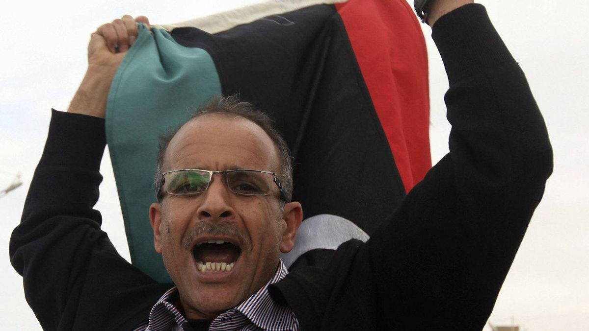 A man celebrates after hearing news of the arrest of Saif al-Islam Gaddafi, in Benghazi November 19, 2011. A spokesman for Libya's outgoing interim government said on Saturday that Saif al-Islam Gaddafi would be tried in the country rather than being sent to The Hague.