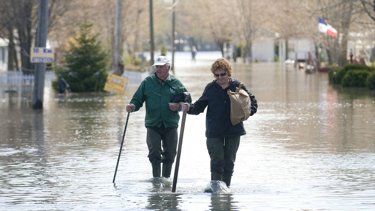 A man and woman wade through flood waters at a campground just outside the town of Saint-Jean-Sur-Richelieu, Que., Sunday, May 8, 2011.