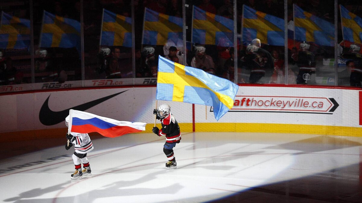 Minor hockey players carry flags before the game between Russia and Sweden during their earlier round-robin game. The two teams clash for the gold-medal Thursday night.