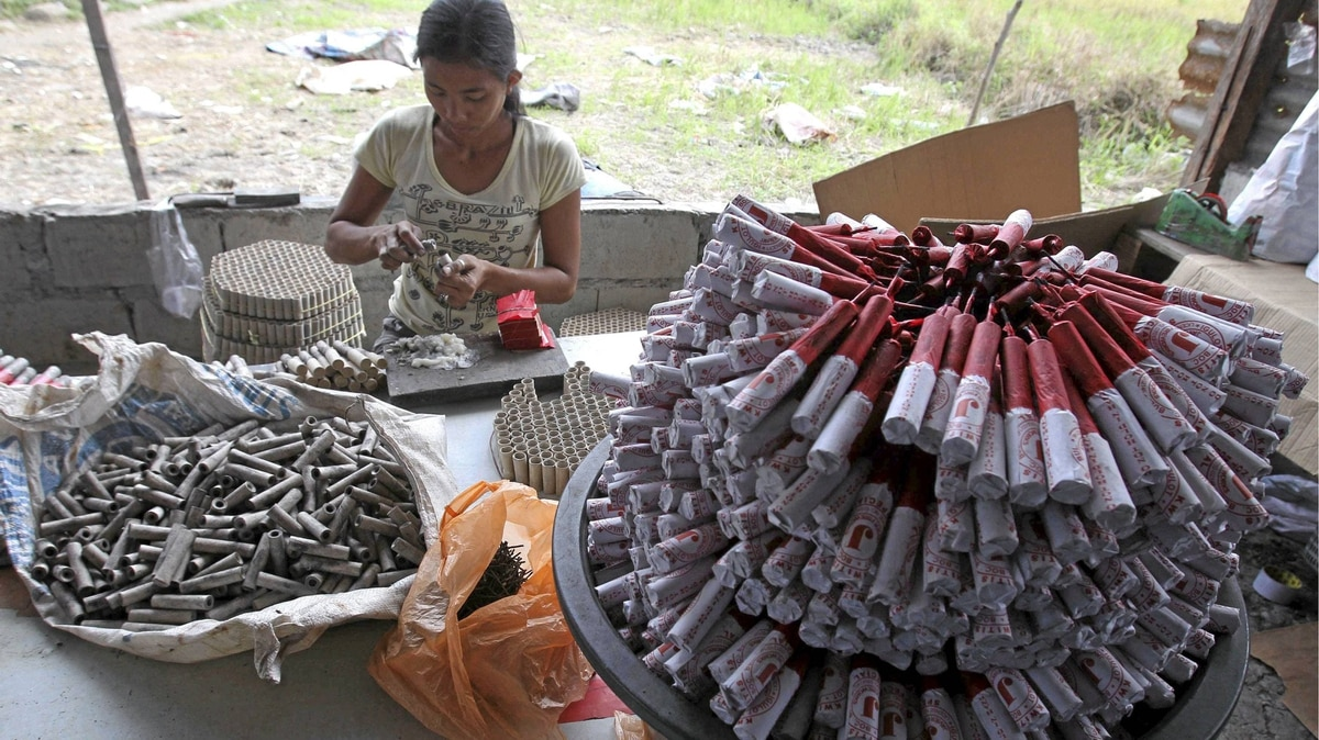 A woman makes firecrackers in a backyard factory in Bocaue town in Bulacan province, north of Manila Dec. 26, 2011.