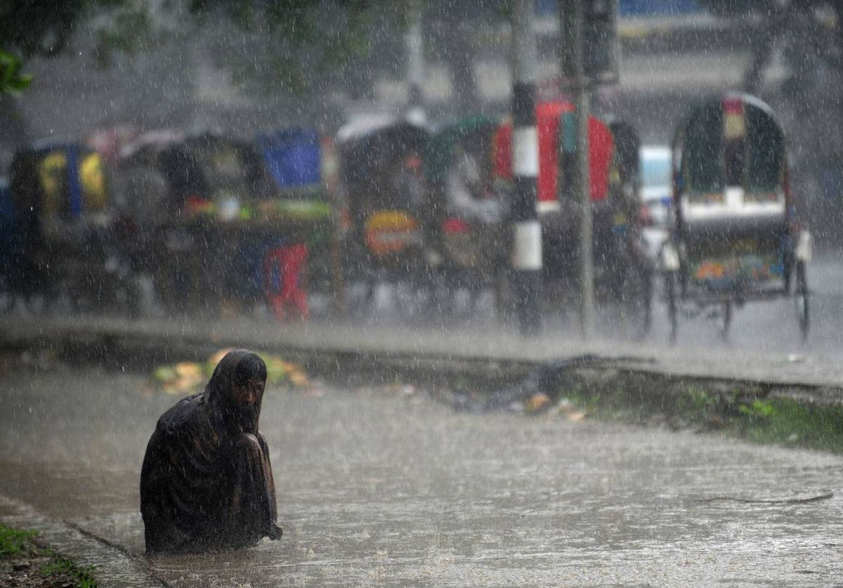 A Bangladeshi homeless man sits on the side of a road during a seasonal rainfall in Dhaka.