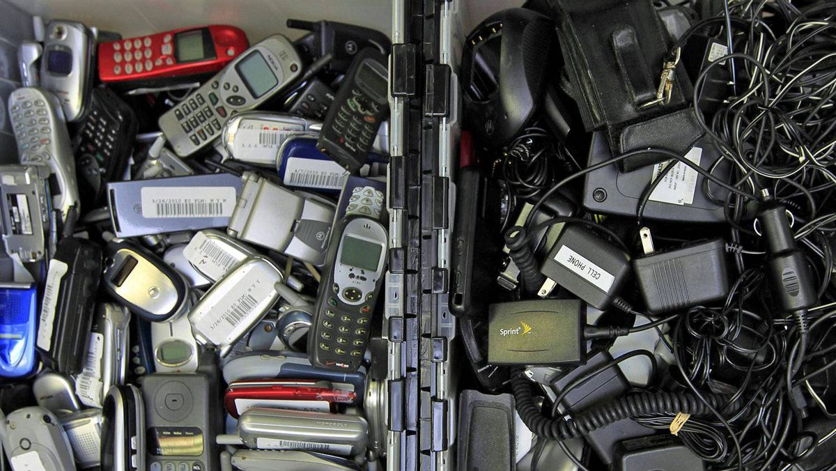 Hundreds of used cellphones and chargers sit waiting to be recycled at a San Diego start-up company, in April of 2010.