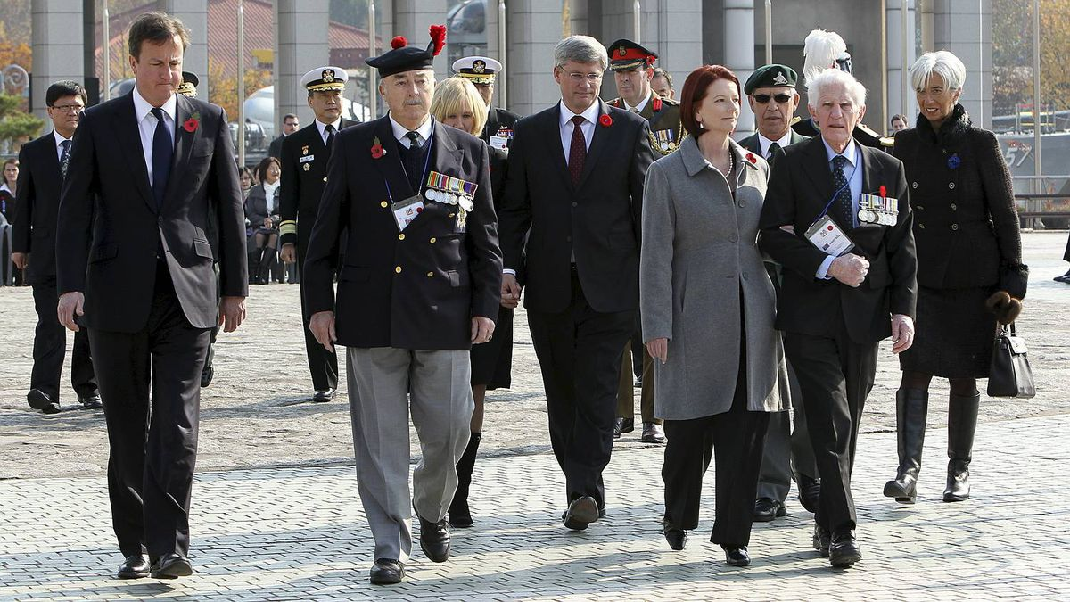 Britain's Prime Minister David Cameron, left,, Australia's Prime Minister Julia Gillard, third right, Prime Minister Stephen Harper and French Finance Minister Christine Lagarde, far right, escort veterans as they take part in a Remembrance Day ceremony at the War Memorial Gloster Valley, at Solma-ri north of Seoul.