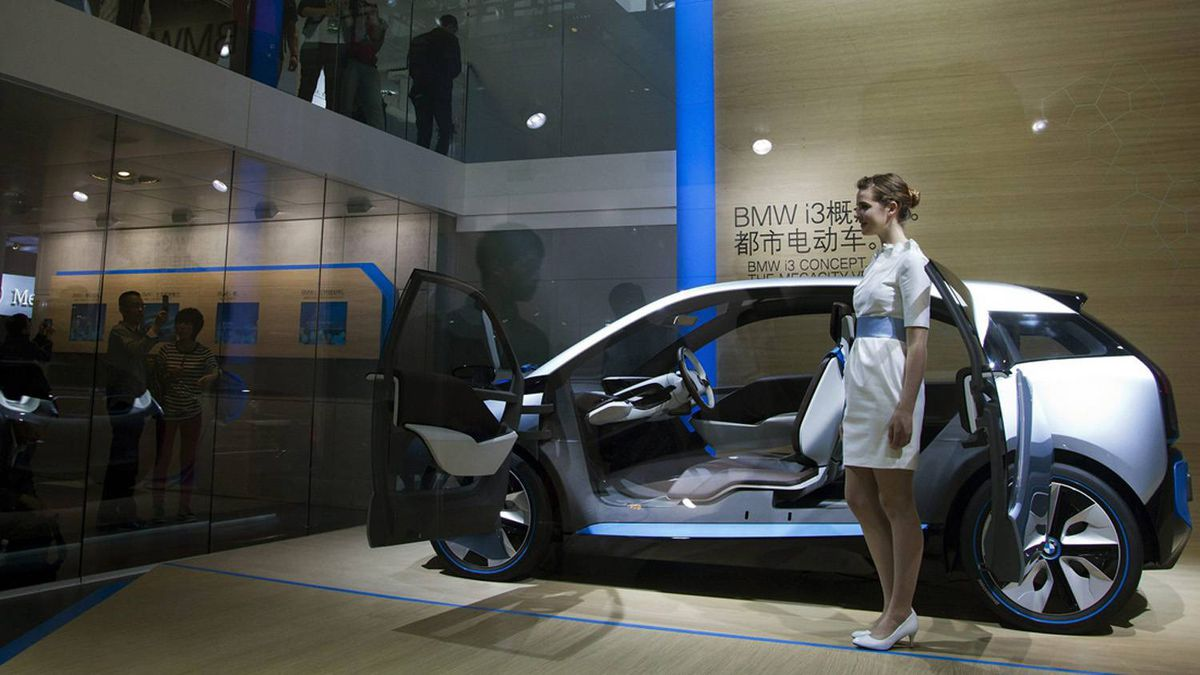 Visitors look at a model standing next to a BMW i3 concept car.