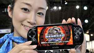 "A model displays Sony Computer Entertainment's new portable videogame console ""PlayStation Vita"", while visitors try it out at the annual Tokyo Game Show in Chiba, suburban Tokyo on September 15, 2011. Sony will release its next-generation PS Vita in Japan on December 17."