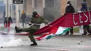 A rioter kicks a projectile as the Quebec Liberal Party is meeting Friday, May 4, 2012 Victoriaville, Quebec.