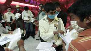 Mexican passengers prepare their papers before getting to the counter of Air Canada in Mexico City April 30, 2009.