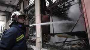A firefighter extinguishes a smouldering building in central Athens on Monday Feb. 13, 2012. Firefighters are dousing smoldering buildings and cleanup crews are sweeping rubble following a night of rioting in central Athens.
