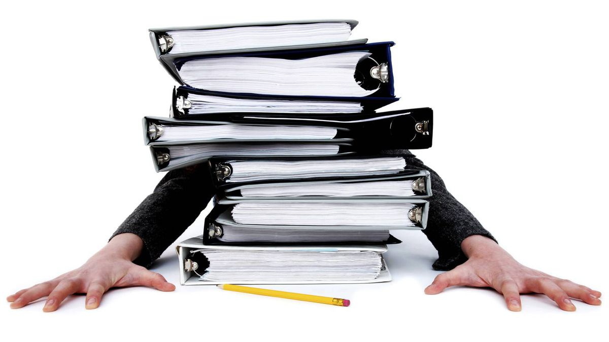 A stack of binders burying a person.