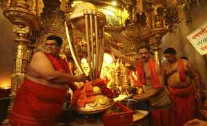 Indian Hindu priests hold a replica of the Cricket World Cup trophy during a special prayer organised to seek blessings of Hindu god Lord Ganesha for the victory of the Indian cricket team in the tournament, at the Siddhivinayak Temple in Mumbai on Feburary 17, 2011.