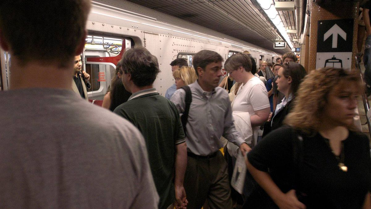 Commuters return to their regular routines Monday morning on the Toronto subway. Most workers in the city were expected back at work for the first time since the blackout last Thursday and the transit system was ready to take them there.