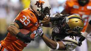 B.C Lions running back Andrew Harris attempts to run the ball past linebacker Clint Kent.