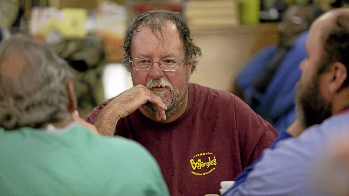 """Kevin Parham, 47, centre, talks with friends while eating dinner at Rowan Helping Ministries, a homeless shelter in Salisbury, N.C., on Mon., Oct. 31, 2011. """""""