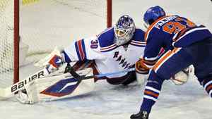 New York Rangers' goalie Henrik Lundqvist (L) makes a save against Edmonton Oilers' Magnus Paajarvi during their NHL hockey game in Edmonton October 22, 2011. The Oilers won 2-0. REUTERS/Dan Riedlhuber