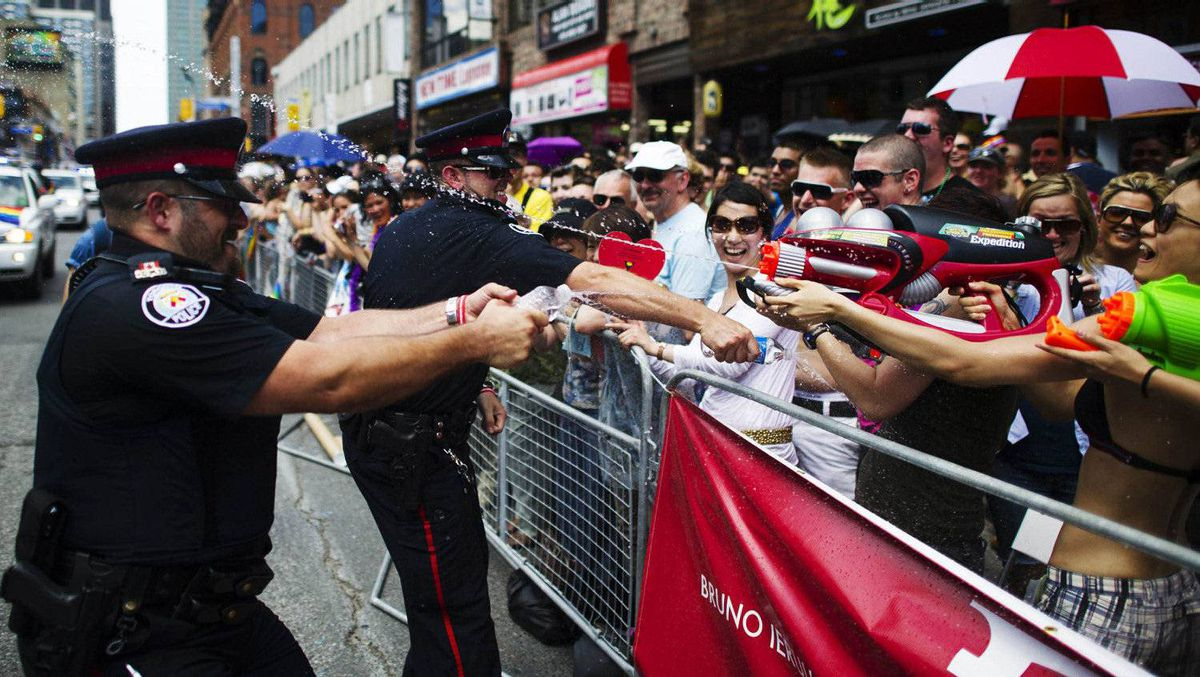 Police officers spray the crowd with water as they take part in the Gay Pride Parade.
