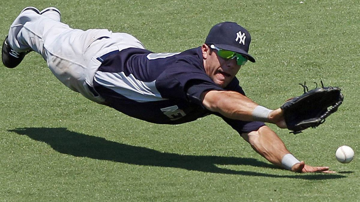 New York Yankees center fielder Austin Krum dives but cannot make the play on a two-RBI triple by Minnesota Twins Matt Tolbert during the second inning of a spring training baseball game in Fort Myers, Fla., Sunday, March 27, 2011. (AP Photo/Charles Krupa)