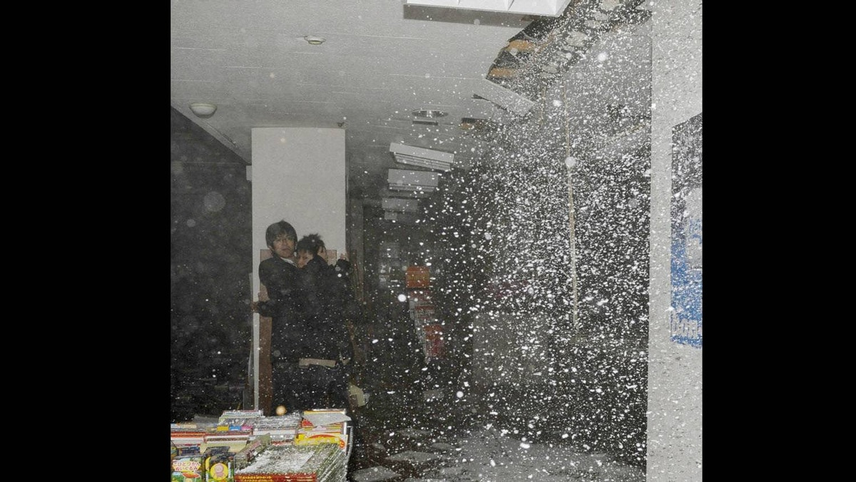 People take shelter as a ceiling collapses in a bookstore during an earthquake in Sendai, northeastern Japan.