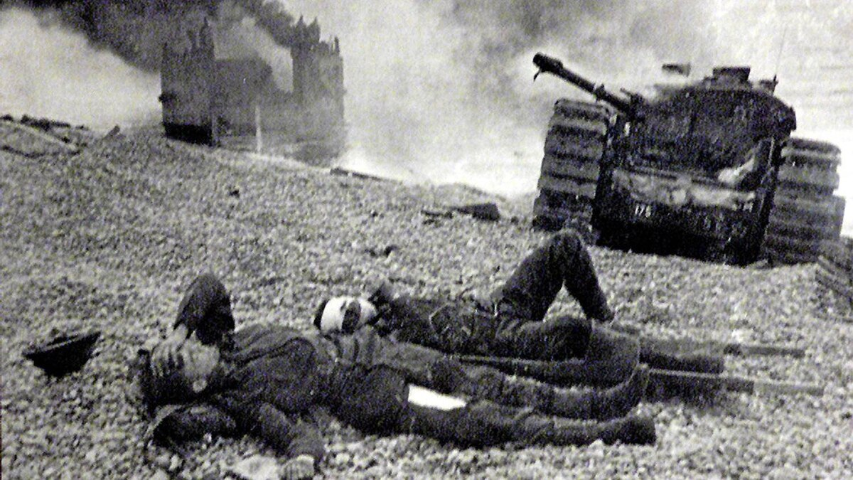 Two wounded Canadian soldiers lie on the pebble beach of Dieppe on August 19, 1942 as a tank and landing craft burn. Sixty years ago Canadian forces, supported by British commandos and American Rangers, launched a raid on the German-occupied French coast around Dieppe at a cost of 913 men. Of the 4,963 Canadians who embarked for the operation only 2,210 returned to England, and many of these were wounded.