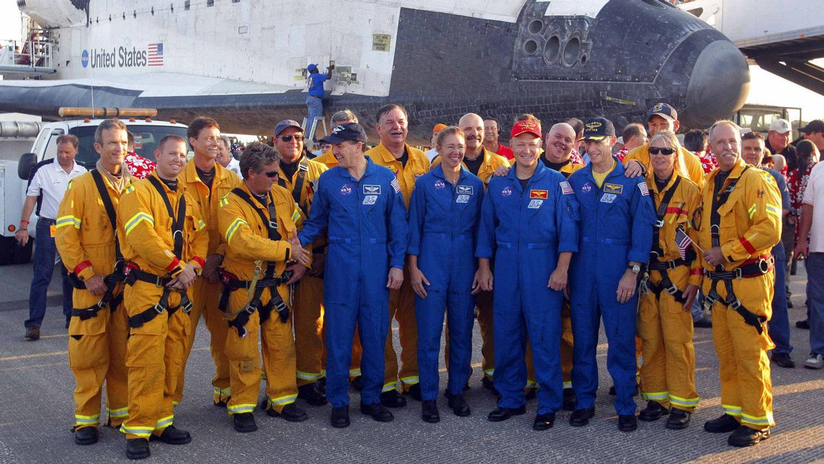 Space shuttle Atlantis crewmembers (L-R) Mission Specialist Rex Waldheim, Mission Specialist Sandra Magnus, Pilot Doug Hurley and Mission Commander Chris Ferguson stand together with firefighters after landing at the Kennedy Space Center in Cape Canaveral, Florida, July 21, 2011.