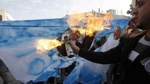 Palestinians burn a mock Israeli national flag with the word Al Jazeera during a protest outside the television channel's offices in the West Bank city of Ramallah January 24, 2011.