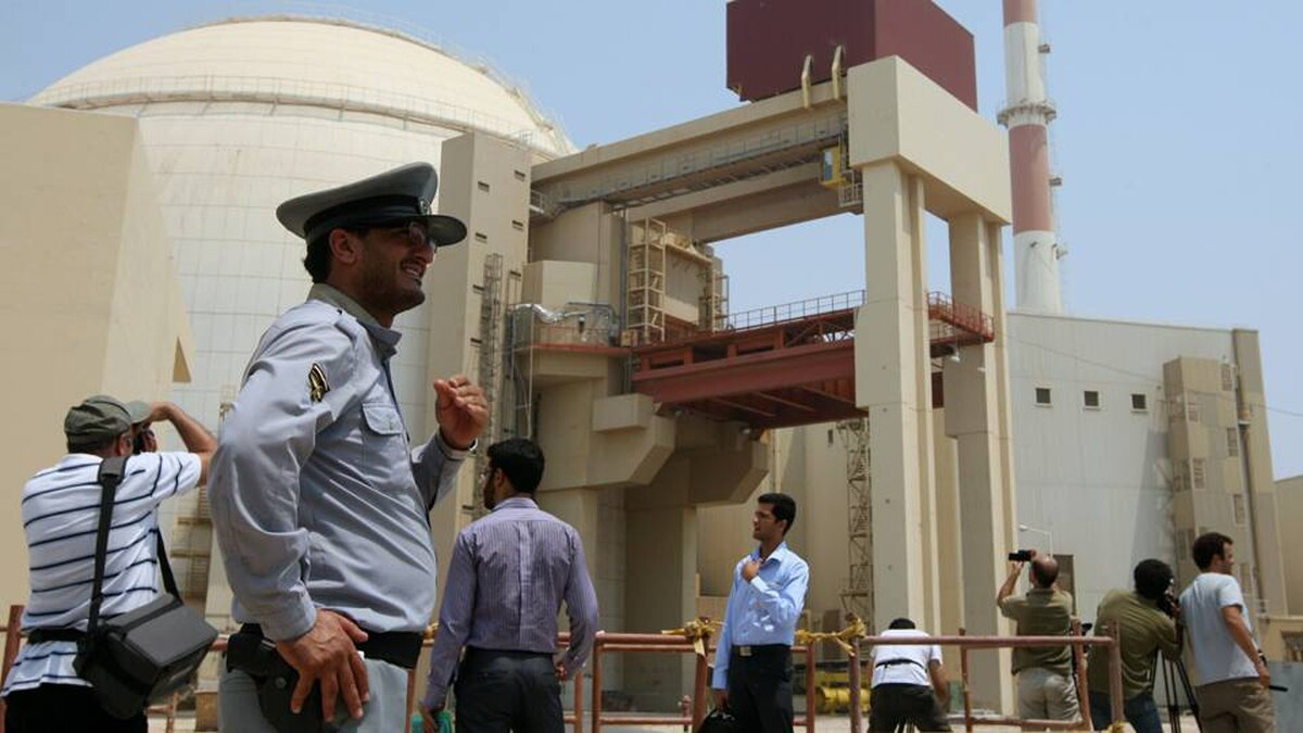"An Iranian security man stands next to journalists outside the reactor building at the Russian-built Bushehr nuclear power plant in southern Iran on August 21, 2010. The Stuxnet computer worm has infected 30,000 computers in Iran but has failed to ""cause serious damage, "" Iranian officials were quoted as saying on September 26, 2010."