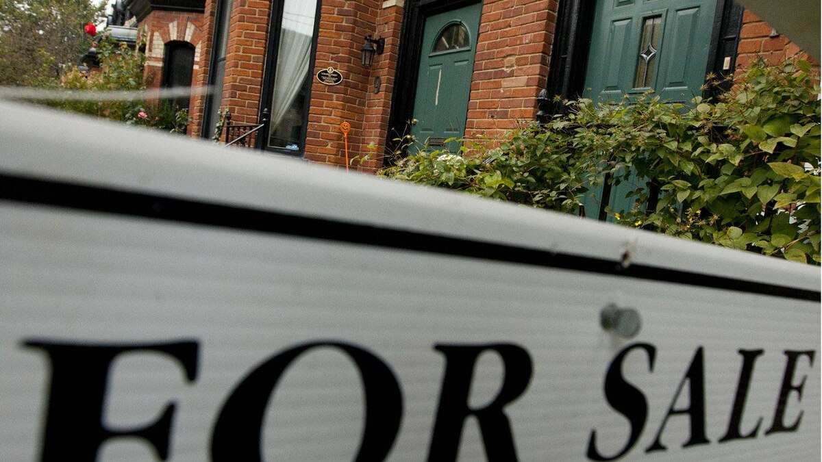 """A """"For Sale"""" sign is posted outside of at Toronto townhome"""