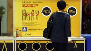 A passenger reads a carry on restriction sign in the departures area of Pearson Airport in Toronto, January 7, 2010.