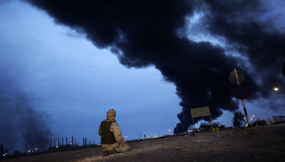 In this photo taken during a government-organised visit for foreign media, a pro-Gadhafi fighter makes his evening prayers in the desert as a plume of smoke rises from the burning oil refinery in Ras Lanouf.