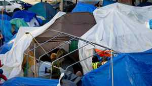 Protesters, including one using a hockey stick, take down a tarp at the Occupy Vancouver site in downtown Vancouver, B.C., on Friday November 4, 2011. Fire officials ordered the removal of unoccupied tents and overhead tarps at the site, citing safety concerns.