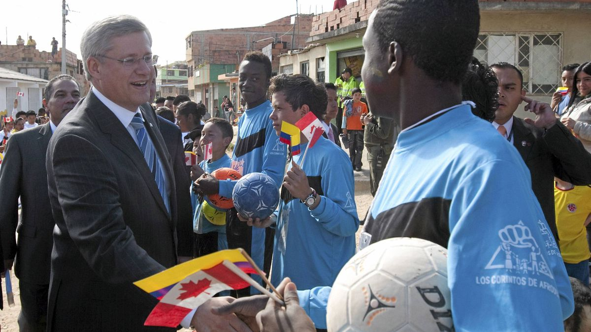 Canadian Prime Minister Stephen Harper shakes hands with a soccer player as he visits the Soacha Youth Development Centre in Soacha, Colombia, Aug. 10, 2011.