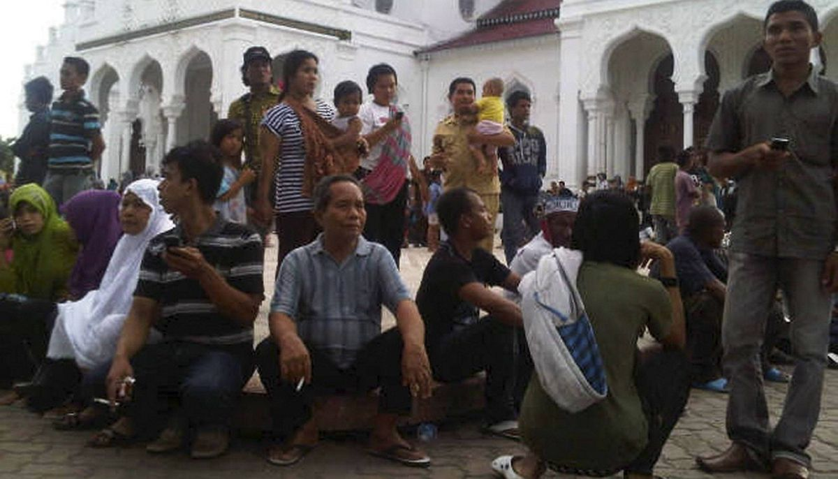 People gather outside the Baiturrahman mosque after an earthquake hit Banda Aceh April 11, 2012. An 8.7 magnitude earthquake struck off Indonesiaon Wednesday, sending residents around the region scurrying from buildings and raising fears of a huge tsunami as in 2004, but authorities said there were no reports suggesting a major threat.
