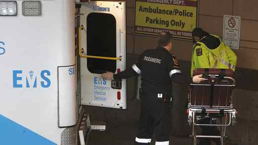 Paramedics move a stretcher out of an ambulance in Toronto on Dec. 19.
