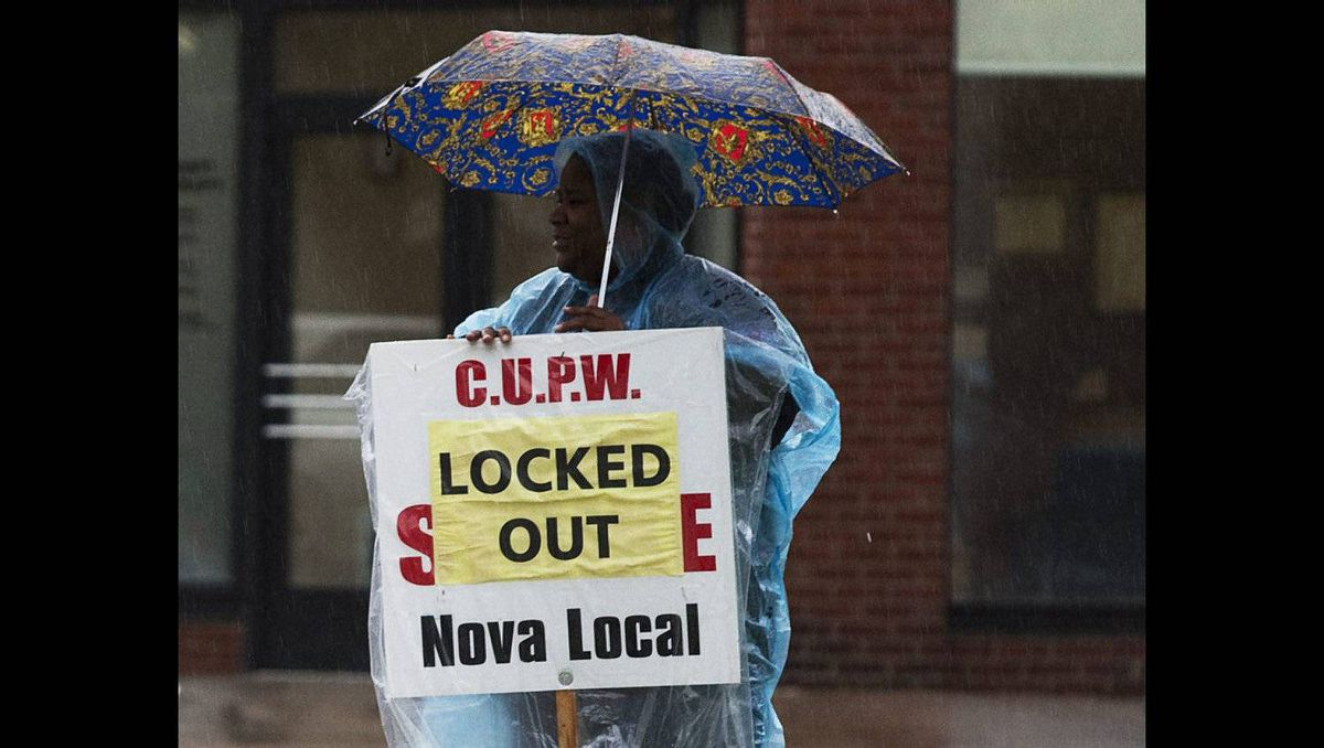 A locked out Canada Post unionized worker stands near the entrance to the main plant in Halifax on June 15, 2011.
