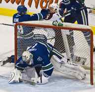 Vancouver Canucks Aaron Rome, left, punches Colorado Avalanche Cody McLeod after the two fell to the ice, knocking the net into Canucks goalie Roberto Luongo during the first period in Vancouver.