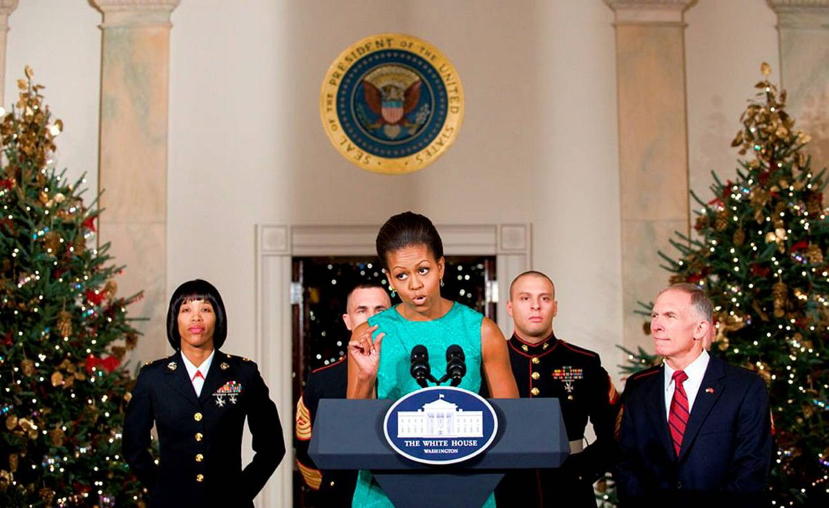 U.S. First Lady Michelle Obama speaks in the Grand Foyer of the White House alongside members of the US.. Marine Corps and Toys for Tots president retired Lieutenant General H.P. Pete Osman (R) as she thanks volunteers who decorated the White House.