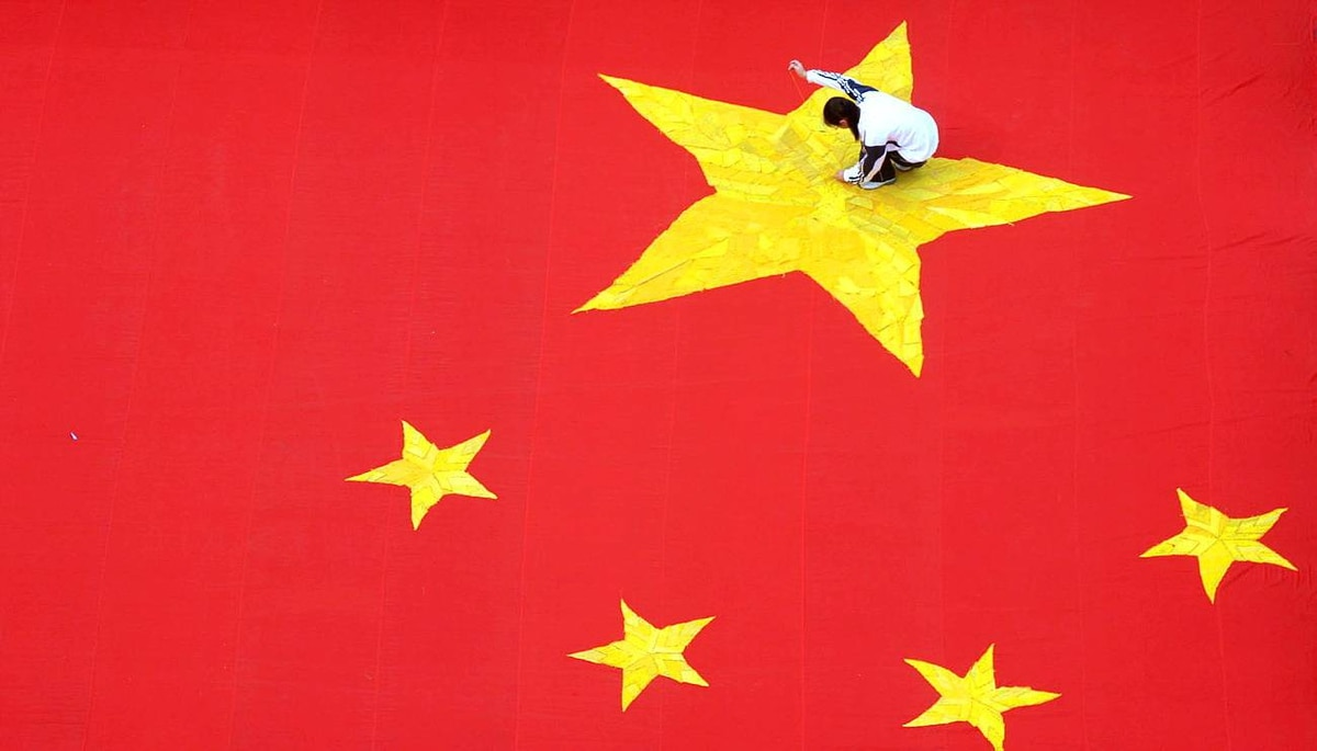 A student embroiders a five-pointed star on a huge Chinese national flag at a college in Jinan, Shandong province, on Sept. 26, 2009.