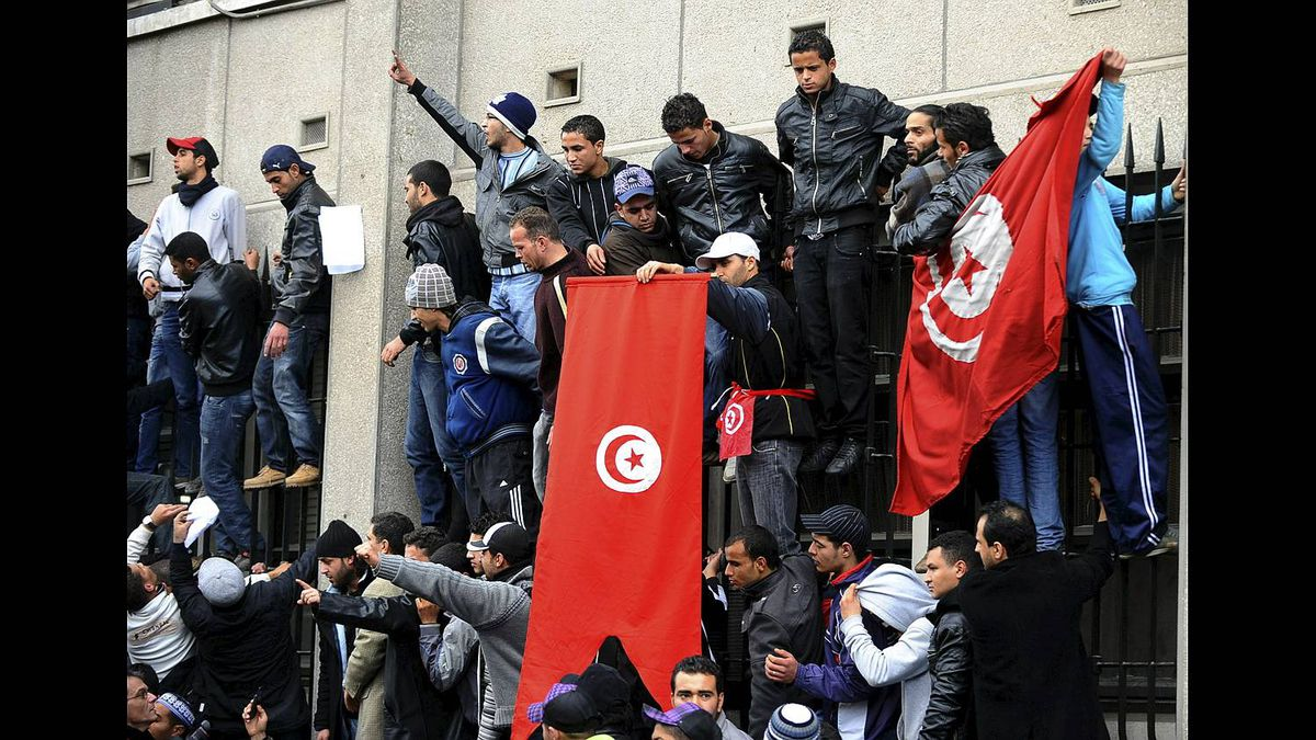 Tunisian demonstrators stand upon railings outside the Interior ministry in Tunis on Jan. 14, 2011.