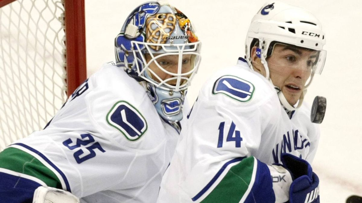 Vancouver Canucks' forward Alexandre Burrows (R) watches the puck as goalie Cory Schneider (L) looks on after a shot by the Colorado Avalanche in the third period in their NHL hockey game in Denver.