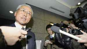 A lawyer for corporate pension fund manager AIJ Investment Advisors Co. speaks with reporters at the building housing the office of the company, after the Financial Services Agency ordered the company to suspend its business for one month earlier in the day, in this photo taken by Kyodo February 24, 2012.