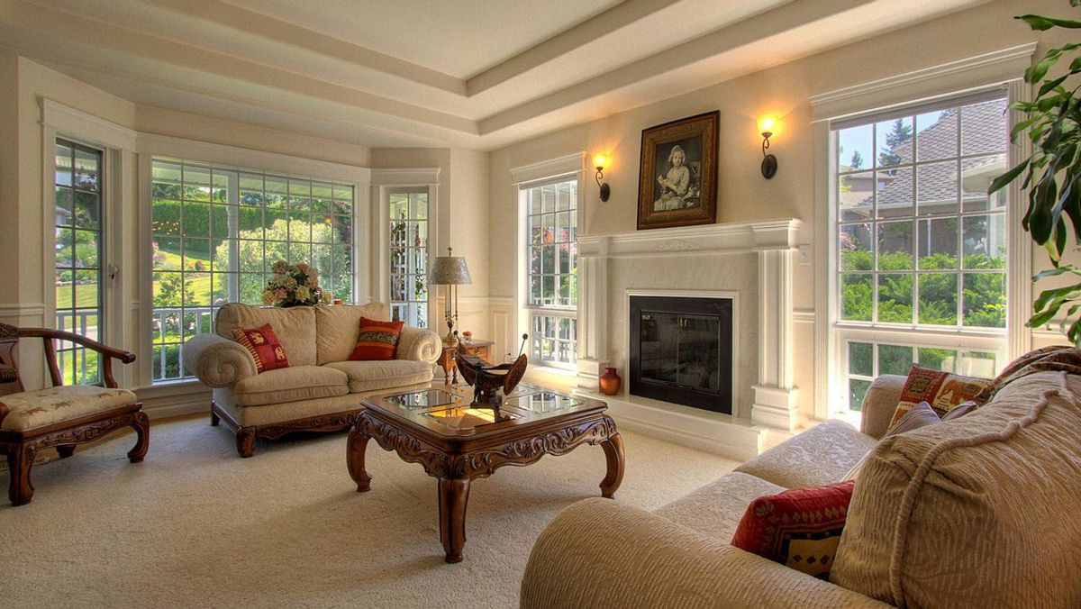 The sun-filled living room features a gas fireplace and new carpeting.