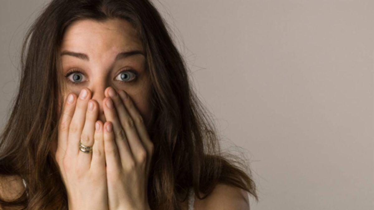A surprised woman puts her hands to her mouth. From Photos.com
