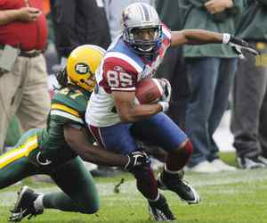 Montreal Alouettes' Brian Bratton, right, gets tackled by Edmonton Eskimos' Kelly Malveaux during the first half of CFL action at Edmonton's Commonwealth Stadium on Thursday, July 30, 2009. THE CANADIAN PRESS/Jimmy Jeong